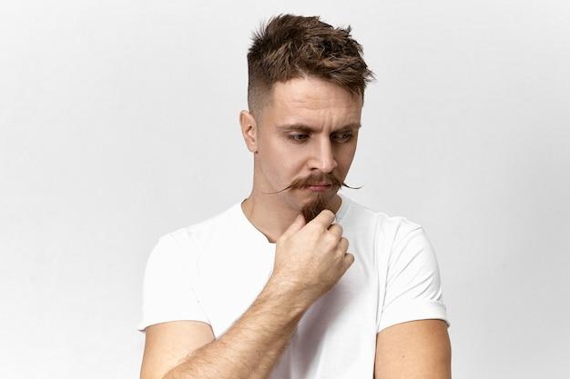 Pojedyncze ujęcie zamyślonego, poważnego faceta hipster ze śmiesznym wąsem, patrzącego w dół z zamyślonym wyrazem twarzy, dotykającego brody kozia bródka, mającego jakiś problem, szukającego sposobu na jego rozwiązanie