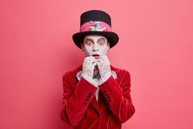 Pojedyncze ujęcie zmartwionego mężczyzny przebranego za szalonego kapelusznika wpatruje się w aparat w kostium, a duży kapelusz świętuje święta przygotowujące się do karnawału odizolowane na różowej ścianie