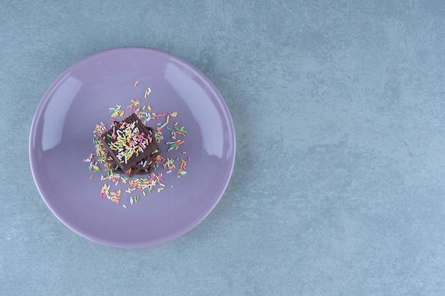 Pojedyncze wafelki czekoladowe z posypką na fioletowym talerzu.
