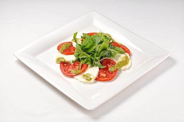 Pojedyncze zdjęcie białego talerza z sałatką caprese - idealne na bloga o jedzeniu lub w menu