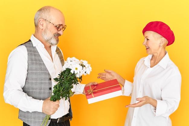 Pojedyncze zdjęcie pięknej europejskiej dojrzałej pani otrzymującej pudełko cukierków i polnych kwiatów od jej starszego chłopaka w eleganckie ubrania i okulary. nieśmiały starszy mężczyzna robi prezent urodzinowy swojej żonie