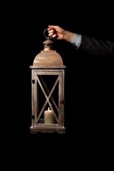 Pojedyncze zdjęcie. ręka trzyma starą lampę z świeczką