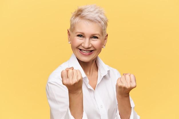 Pojedyncze zdjęcie silnej niezależnej europejskiej bizneswoman z krótkimi farbowanymi włosami, wyrażającej pozytywne nastawienie, uśmiechającej się pewnie i zaciskającej pięści. kobiety, kobiecość, siła, pewność siebie i sukces