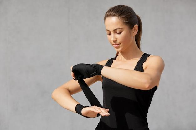 Pojedyncze zdjęcie szczupłej kobiety w bandażach bokserskich, ma ciemne włosy czesane w koński ogon, ubrane w swobodną czarną koszulkę