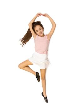 Pojedyncze zdjęcie z wysokiego punktu widzenia słodkiej dziewczyny leżącej na podłodze i udając, że tańczy balet