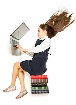 Pojedyncze zdjęcie z wysokiego punktu widzenia uroczej uczennicy siedzącej na książkach i korzystającej z laptopa
