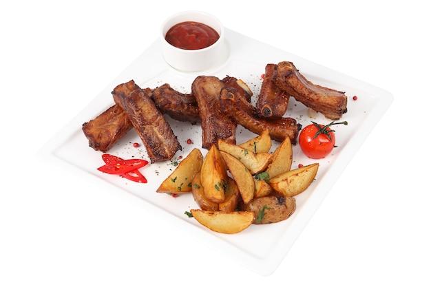 Pojedyncze żeberka wieprzowe z klinami ziemniaków na białym kwadratowym półmisku obsługujących, na białym tle.