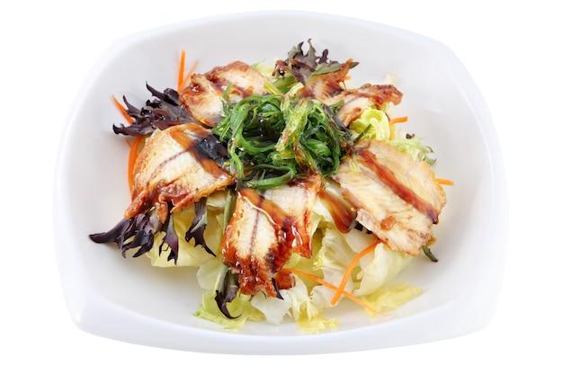 Pojedynczo na białym głębokie miski z plastrami wędzonego węgorza, leżącego na liściach świeżej sałatki, ozdobione wodorostami chuka.