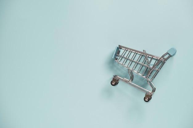Pojedynczo na zakupy wózek na niebieskim tle i przestrzeni kopii, zakupy online i koncepcja e-commerce.
