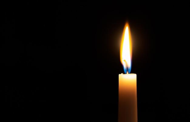 Pojedynczo zapalona świeca z dość płomienistym płomieniem na czarnej powierzchni