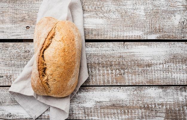 Pojedynczy biały chleb na płótnie z drewnianym tłem