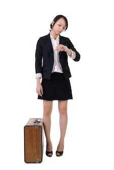 Pojedynczy biznes dziewczyna czeka i ogląda czas ze starym etui podróżnym, portret pełnej długości na białym tle.