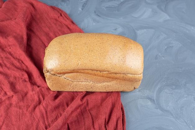 Pojedynczy bochenek chleba na czerwonym obrusie na marmurowej powierzchni.