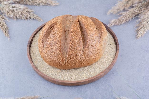 Pojedynczy bochenek chleba na tacy wypełnionej sezamem, otoczony suszonymi łodygami trawy piórkowej na marmurowej powierzchni