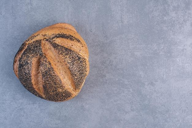 Pojedynczy bochenek chleba powlekanego czarnym sezamem na marmurowym tle. zdjęcie wysokiej jakości