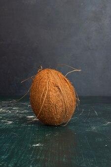 Pojedynczy cały kokos na marmurowym stole.