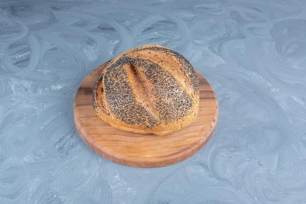 Pojedynczy chleb pokryty czarnym sezamem na marmurowym stole.