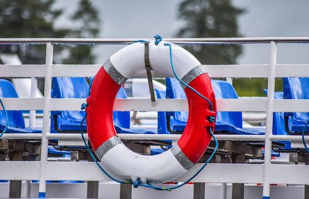 Pojedynczy czerwony i biały koło ratunkowe na łodzi gotowy do użycia, windermere, lake district