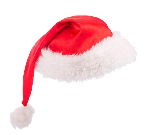 Pojedynczy czerwony kapelusz świętego mikołaja na białym tle na białej powierzchni