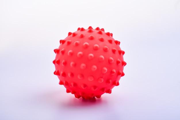 Pojedynczy czerwony kolorowy jasny na białym tle kolczasta piłka, makro