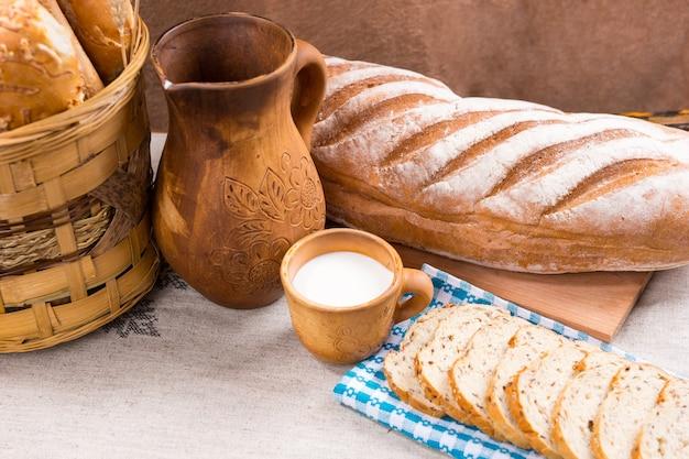 Pojedynczy drewniany dzban, pełna szklanka mleka i chleba jako cały bochenek i kromki obok kosza na stole