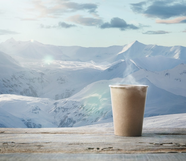 Pojedynczy kubek herbaty lub kawy i krajobraz gór na tle. kubek gorącego napoju ze śnieżnym spojrzeniem i zachmurzonym niebem przed nim. ciepło w zimowy dzień, święta, podróże, nowy rok i boże narodzenie.