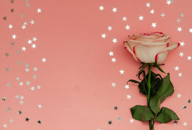Pojedynczy kwiat róży z gwiazdami holograficznymi na różowym tle z miejscem na tekst