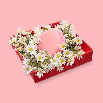 Pojedynczy makaronik w czerwonym pudełku prezentowym