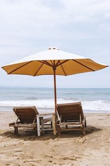 Pojedynczy parasol z dwoma leżakami na pustej plaży.