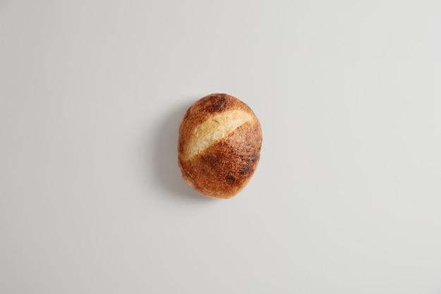 Pojedynczy pieczony okrągły domowy orkiszowy chleb wypiekany z organicznej mąki, na białym tle na tle białego studia. wyśmienity produkt piekarniczy. bochenek chrupiącego wiejskiego chleba na zakwasie. zdrowe odżywianie. koncepcja żywności