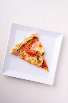 Pojedynczy pizza plasterek na bielu talerza odgórnym widoku