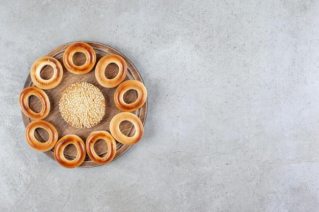 Pojedynczy plik cookie otoczony sushki na drewnianej desce na tle marmuru. wysokiej jakości zdjęcie
