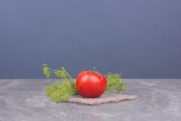 Pojedynczy pomidor na marmurze z ziołami.