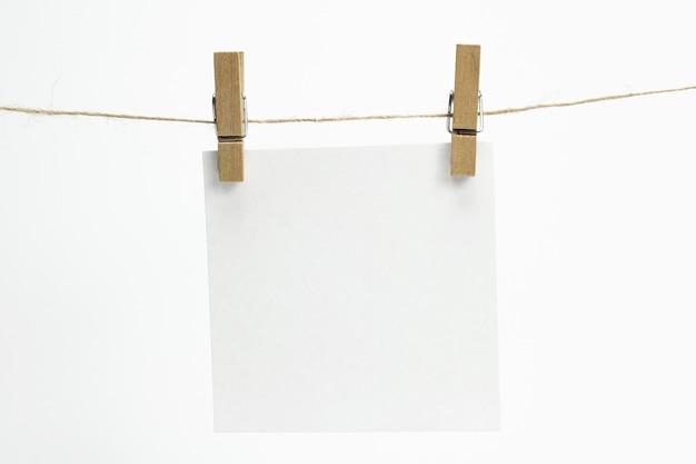 Pojedynczy pusty arkusz papieru na notatki wiszące na linie z spinaczami do bielizny i odizolowane na białym.