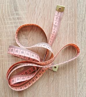 Pojedynczy różowy metr krawiecki na drewnianym stole. przyrząd pomiarowy służący do szycia odzieży i wykonywania pomiarów części ciała