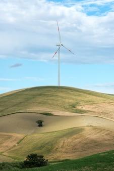 Pojedynczy silnik wiatrowy w ziemi uprawnej na wzgórzu