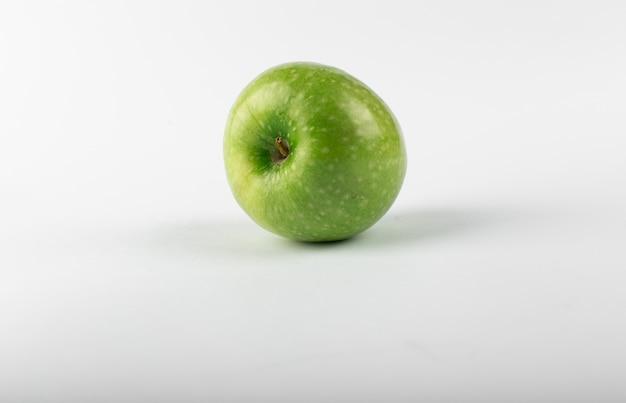 Pojedynczy zielony świeży jabłko odizolowywający na bielu