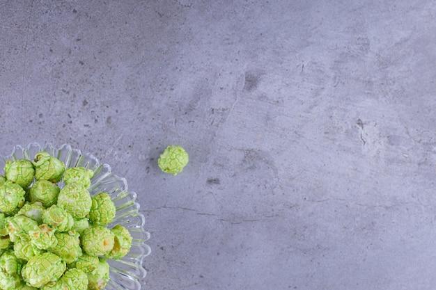 Pojemnik na cukierki zawierający stertę zielonego, smakowego popcornu na marmurowym tle. zdjęcie wysokiej jakości