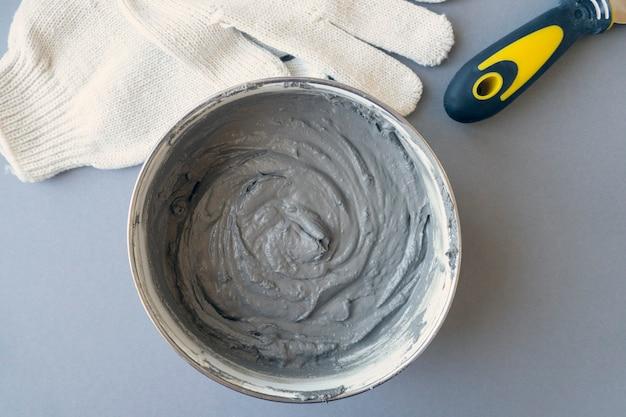 Pojemnik na sprzęt pracownika z szpachlą cementową i rękawicami pracowniczymi na biurku