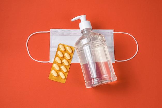 Pojemnik na żel z alkoholem, maska chirurgiczna, lek na czerwono