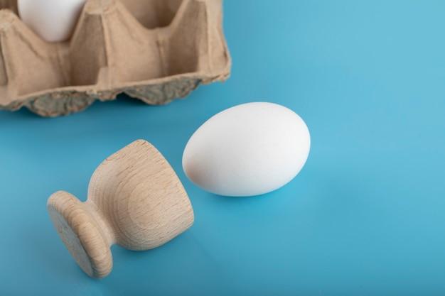 Pojemnik świeżych jaj na niebieskiej powierzchni.