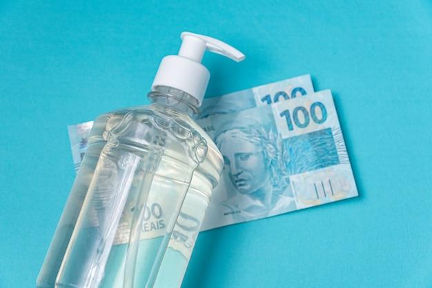 Pojemnik z alkoholem żelowym i brazylijskimi prawdziwymi pieniędzmi,