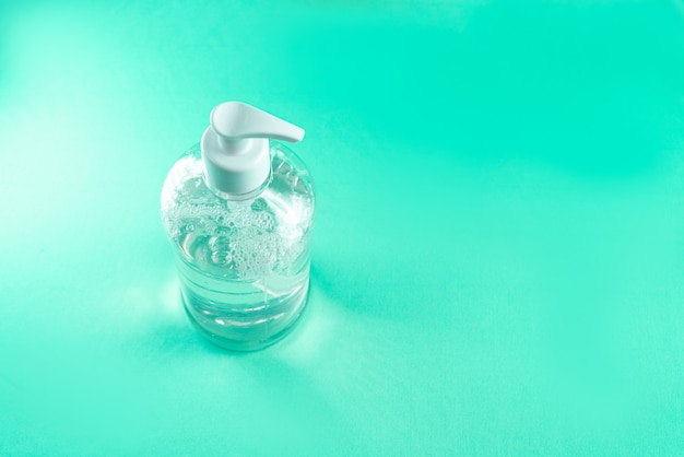 Pojemnik z żelem alkoholowym na jasnoniebieskiej ścianie