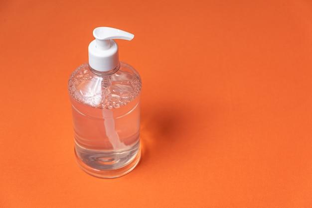 Pojemnik z żelem alkoholowym na pomarańczowej ścianie