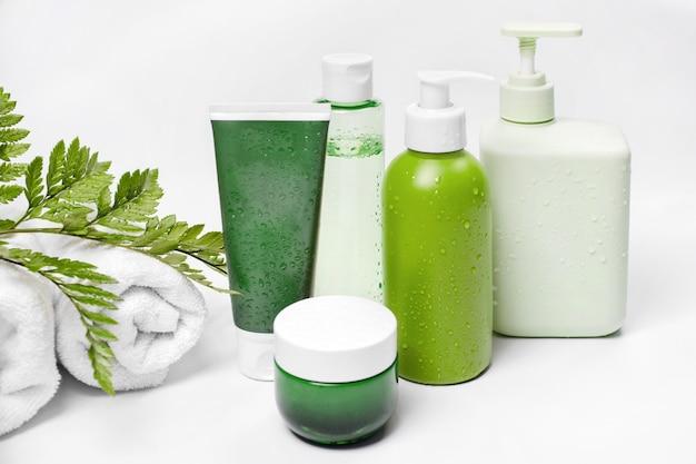 Pojemniki kosmetyczne z zielonymi liśćmi ziołowymi i białymi ręcznikami, puste opakowanie z etykietą na makietę marki. krem nawilżający, szampon, tonik, pielęgnacja skóry twarzy i ciała.