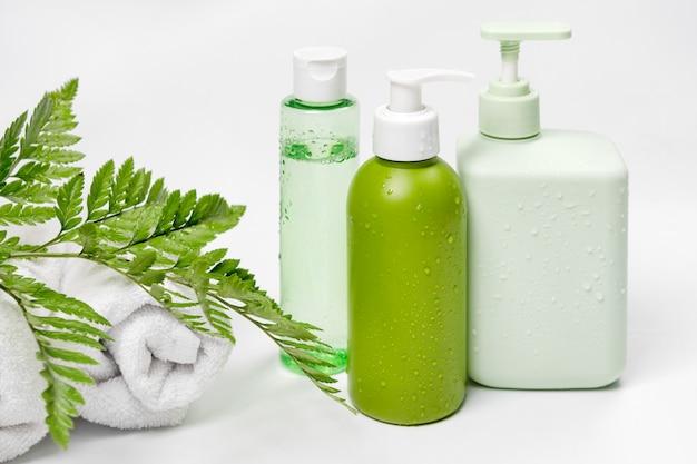 Pojemniki kosmetyczne z zielonymi liśćmi ziołowymi i białymi ręcznikami, puste opakowanie z etykietą na makietę marki. szampon, tonik, mydło w płynie, pielęgnacja skóry twarzy i ciała.