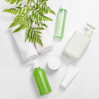 Pojemniki kosmetyczne z zielonymi liśćmi ziołowymi i kroplami wody, puste opakowanie z etykietą na makietę marki. krem nawilżający, szampon, tonik, pielęgnacja skóry twarzy i ciała.