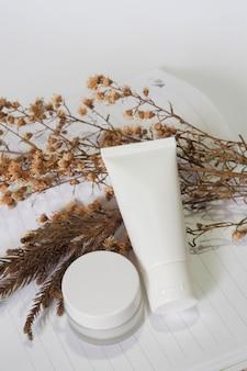 Pojemniki na butelki kosmetyczne biały produkt z suchym kwiatem.