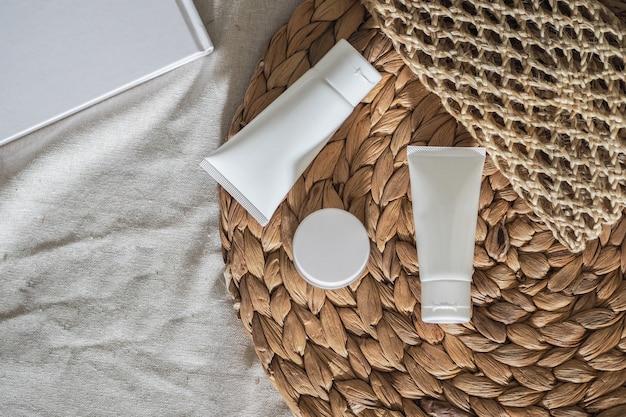 Pojemniki na butelki kosmetyczne, biały produkt z suchym kwiatkiem i plecionymi torebkami.