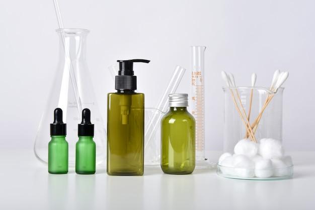 Pojemniki na butelki kosmetyczne i szklane naczynia naukowe, puste opakowanie na branding, farmaceutyczna pielęgnacja skóry przez lekarza dermatologa, badania i opracowanie koncepcji produktu kosmetycznego.